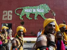 Performers walk at the exhibition centre of the 'Make In India' week in Mumbai