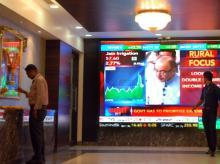 People Bombay Stock Exchange walking past a digital screen showing Arun Jaitley's Budget speech (pic: Kamlesh Pednekar)
