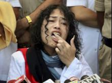 Irom Sharmila licks honey from her hand to break her fast during a press conference