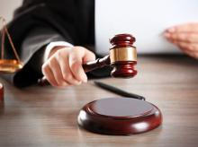 A judge hitting gavel with paper at wooden table. (Photo: Shutterstock)
