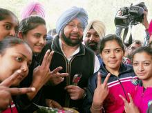 Punjab Congress chief Capt Amarinder Singh flashes victory sign with youngsters at a polling station during voting for Punjag Assembly polls in Patiala. Photo: PTI