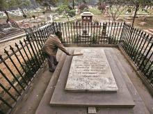 A worker cleans the grave of Johan Nicholson at the Nicholson Christian Cemetery