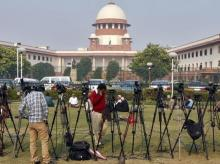 Tripods of television crew stand in front of the Indian Supreme Court building in New Delhi