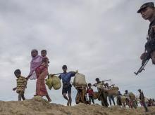 Rohingya Muslims, who spent four days in the open after crossing over from Myanmar into Bangladesh, carry their children and belongings after they were allowed to proceed towards a refugee camp, at Palong Khali, Bangladesh. Photo: AP   PTI