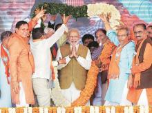 Prime Minister Narendra Modi garlanded by BJP workers during a rally for the Gujarat elections in Gandhinagar. File Photo: PTI