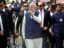 Prime Minister Narendra Modi shows his finger marked with indelible ink, as he leaves after casting his vote