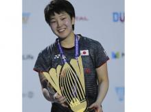 Akane Yamaguchi poses with the trophy after she beat India's Pusarla V. Sindhu in the final match of the Dubai Badminton World Superseries Finals in Dubai