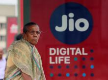 A woman waits at a bus stop with an advertisement of Reliance Industries' Jio telecoms unit in Mumbai on July 11, 2017. (Photo: Reuters)