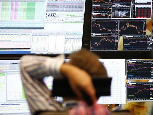 A trader sits in front of the computer screens at his desk at the Frankfurt stock exchange, Germany
