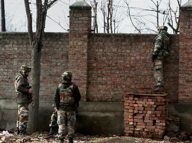 Security forces personnel take position outside the JKEDI building where militants have reportedly taken refuge after launching an attack on a CRPF convoy at Sampora Pampore, near Srinagar. PTI Photo by S Irfan