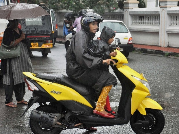A woman-child duo dressed up in raincoats riding a scooter during the pre-monsoon rains in Kochi