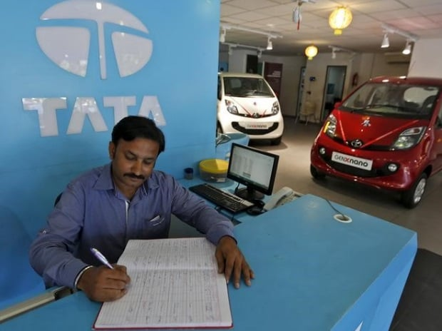 An employee writes on a register inside the Tata Motors car showroom in Ahmedabad