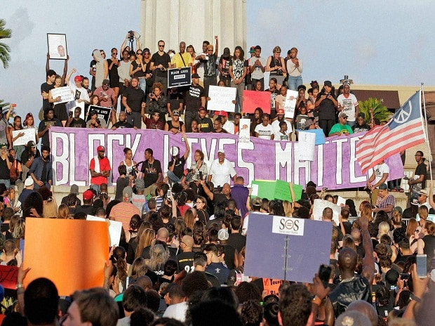People gather for a rally in protest of the shootings of African-American men by police in Minnesota and in Baton Rouge, La., at Lee Circle in New Orleans on Friday  Photo: PTI