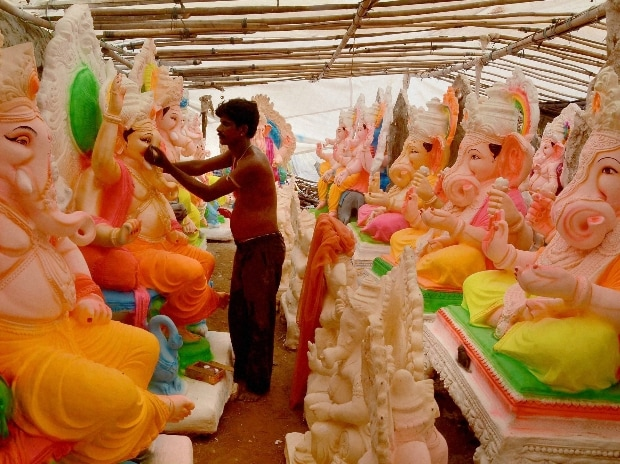 An artist giving touches to an idol of Lord Ganesh