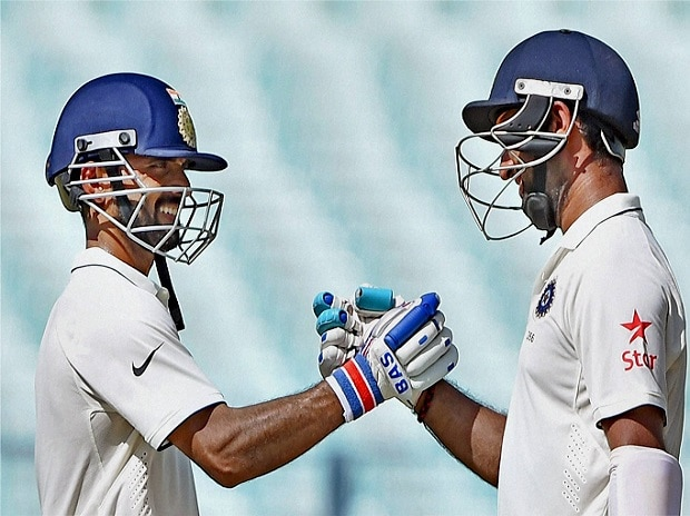 Indian batsman Cheteswar Pujara is greeted by Ajinkya Rahane (L) for his half century during 1st day of 2nd Test Match against New Zealand at Eden Garden in Kolkata. Photo:PTI