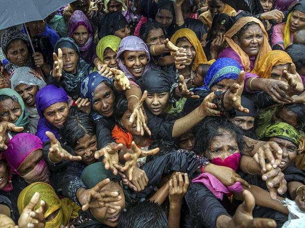 Balukhali : Rohingya Muslim women, who crossed over from Myanmar into Bangladesh, stretch their arms out to collect sanitary products distributed by aid agencies near Balukhali refugee camp, Bangladesh. Photo: PTI