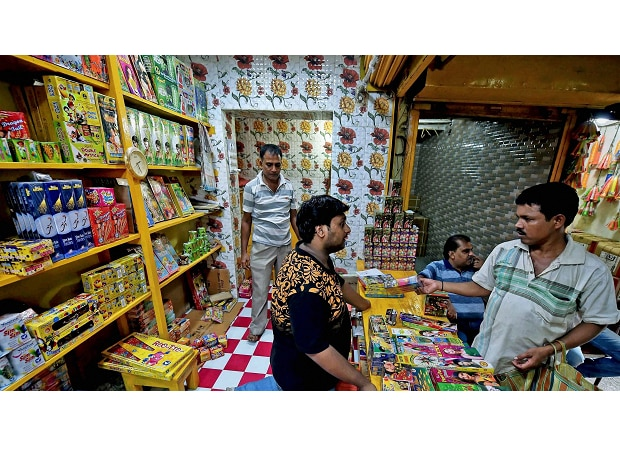 People purchasing fire-crackers at a shop in Kolkata on Friday to celebrate Kali Puja and Diwali. (Photo: PTI)