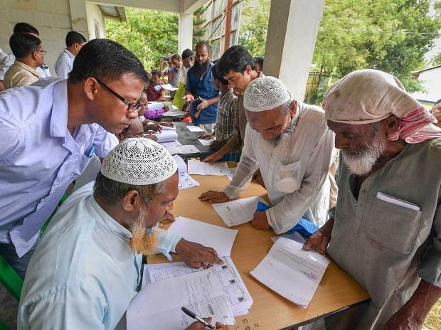 People check their names on the final draft of the state's National Register of Citizens after it was released, at a NRC Seva Kendra in Nagaon on Monday
