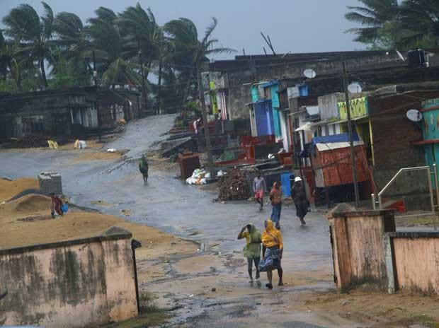 Locals walk near their houses as Cyclone 'Titli' hits the coast, in Ganjam