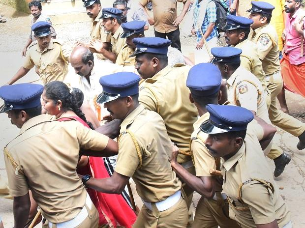 Police escort Madhavi (of Andhra Pradesh) and her family members after she was heckled by the protesters while she was seeking the entry to the Lord Ayyappa Temple on its opening day in Sabarimala, Kerala, Wednesday | Photo: PTI