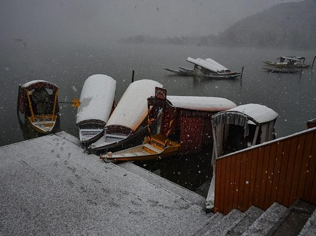 A Shikarawalla clears snow from a boat during season's first Snowfall in Srinagar, Saturday, Nov 3, 2018