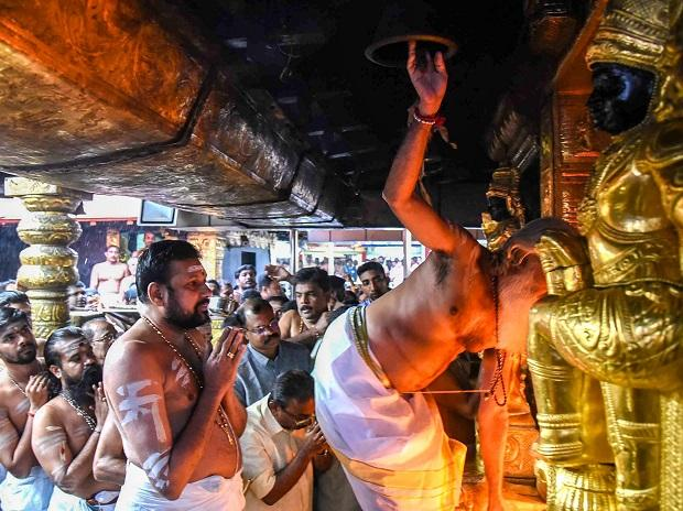 Outgoing chief priest AV Unnikrishnan Namboothiri opens the 'sanctum sanctorum' of the Sabarimala temple as it opens for two-month long pilgrim season in Sabarimala on Friday | Photo: PTI