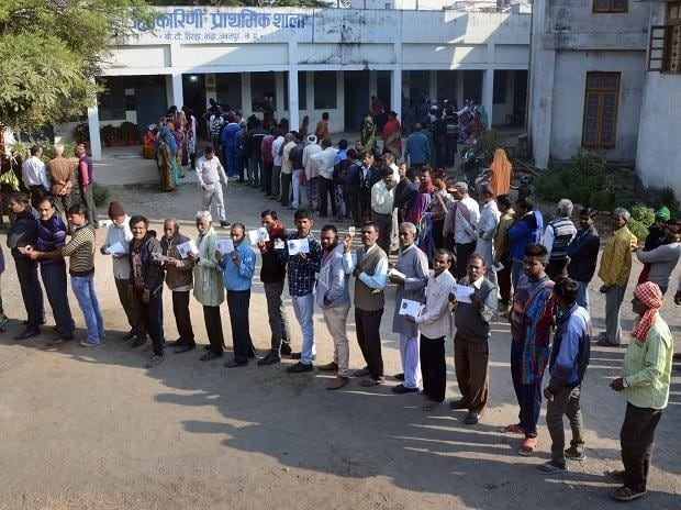 People wait with their identity cards to cast their votes for the Assembly elections, in Jabalpur, Madhya Pradesh. Photo: PTI