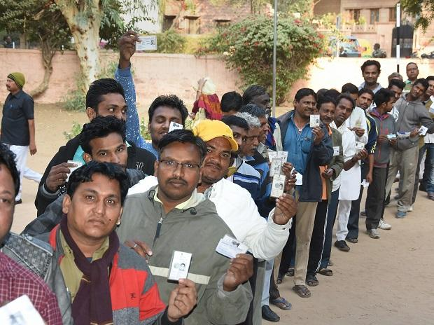 elections, pollsVoters show their identity cards as they stand in a queue at a polling station to cast their vote for the state Assembly elections, in  Jodhpur