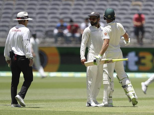 Virat Kohli looks to the umpire after he and opposing captain, Australia's Tim Paine came face to face after Kohli moved into Paine's path during play in the second cricket test between Australia and India in Perth | Photo: AP/PTI
