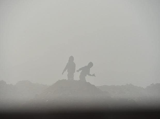 Silhouette of children seen through a layer of dense fog on a cold, winter morning, in New Delhi, Sunday