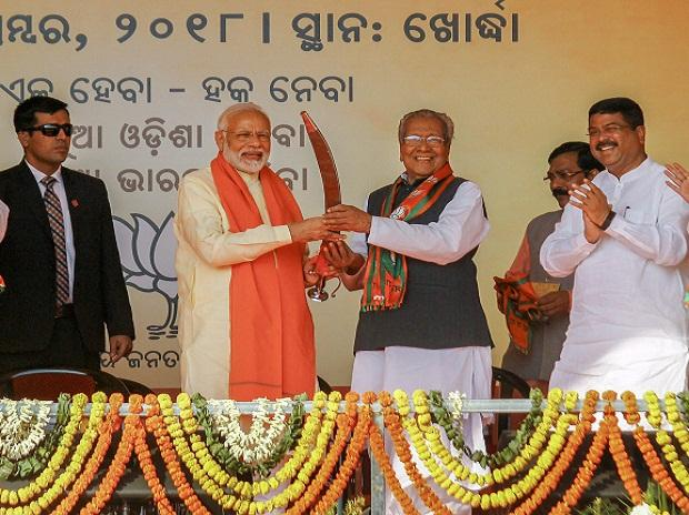 Prime Minister Narendra Modi being presented a memento by BJP workers during a party rally 'Swabhiman Samabesh' near Khurda, Odisha