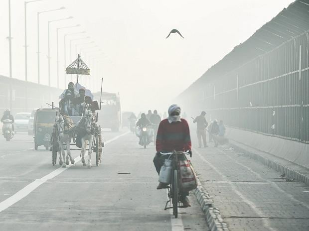Commuters ride through heavy fog on a winter morning, in New Delhi