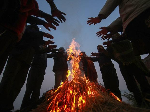 People keep themselves warm around a bonfire during a cold winter morning on the outskirts of Jammu