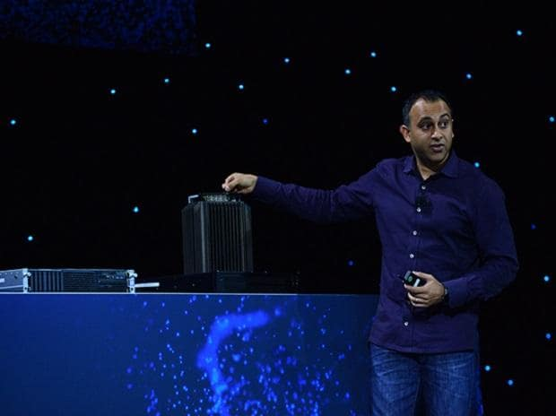 Navin Shenoy, Intel executive vice president in the Data Center Group, motions to a 5G base station prototype during Intel Corporation's news event at CES 2019