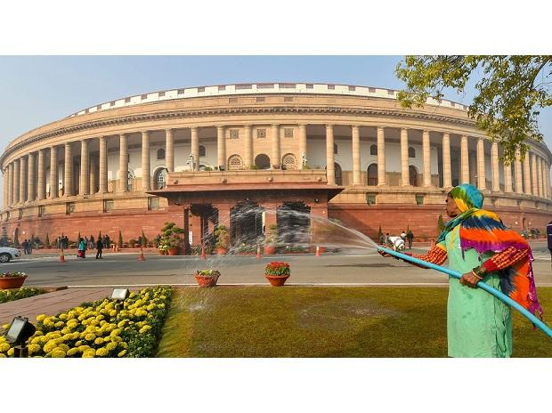 A worker waters plants near the Parliament House during the ongoing Winter Session of Parliament, in New Delhi, Tuesday | Photo: PTI