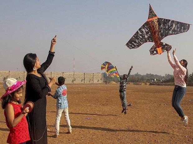 People fly kites on the eve of Makar Sakranti festival