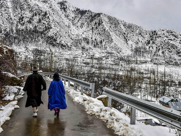 People strolling along a snow-covered path amid light rains