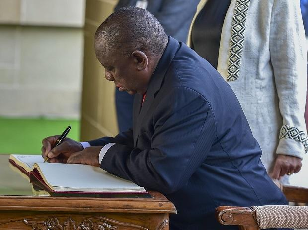 Cyril Ramaphosa writes his message on the visitors book during their visit to Mahatma Gandhi's memorial Rajghat