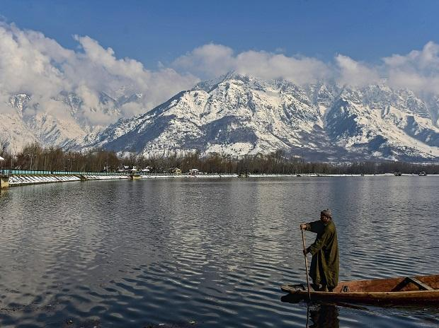 A boatman rows his boat against the backdrop of a snow-clad mountain after a spell of heavy snowfall, in Srinagar