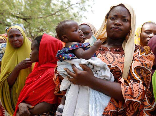 Woman carries her child as she attends to cast her vote during Nigeria's presidential election at Capital School polling unit, in Yola (Photo: Reuters)