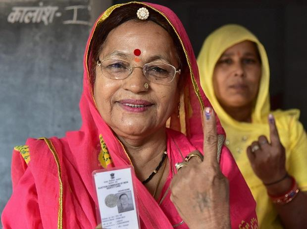 Voters show their identity cards as they stand in a queue at a polling station to cast their vote for the state assembly elections in Jodhpur. Photo: PTI