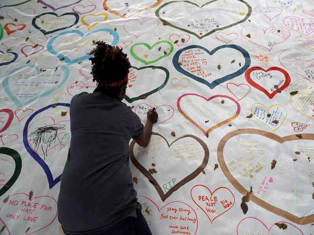 People write on a sign at a memorial as a tribute to victims of the mosque attacks, near a police line outside Masjid Al Noor in Christchurch Photo: Reuters