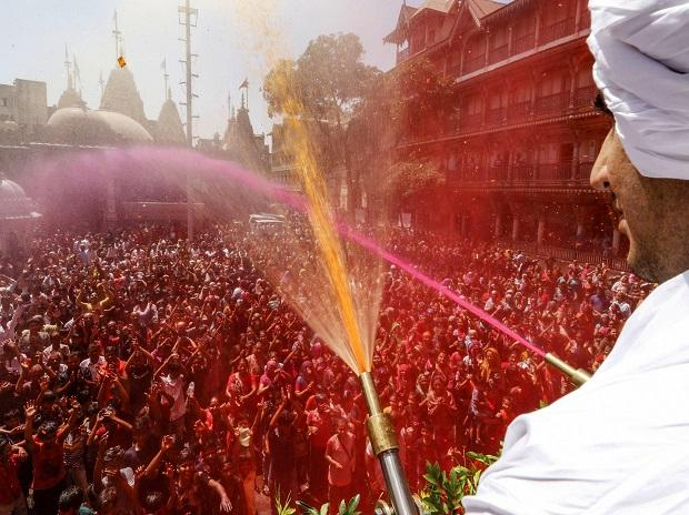 A temple priest sprays color water on devotees at a temple during Holi celebrations in Ahmedabad