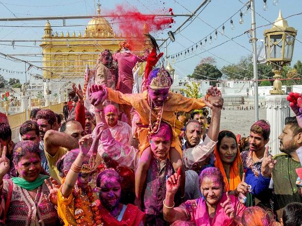 People smear colours at each other during Holi celebrations at Durgiana Temple in Amritsar