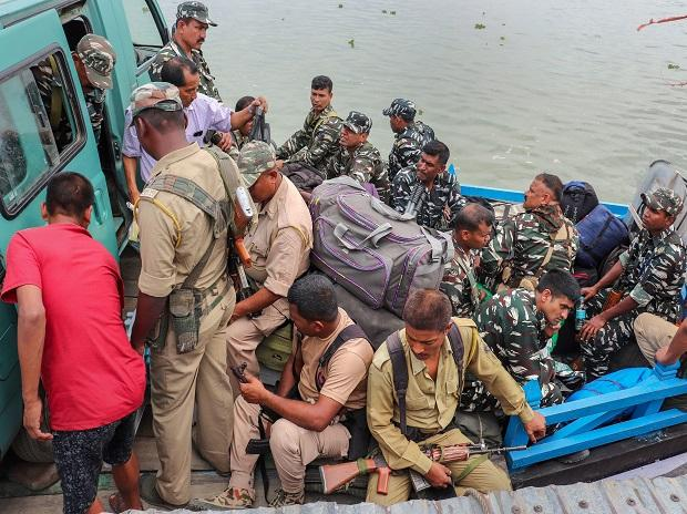 Security personnel head to a polling booth on a ferry ahead of the first phase of Lok Sabha elections in Majuli, Assam