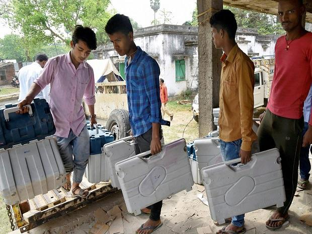 Workers carry boxes containing Electronic Voting Machines (EVM) and Voter Verified Paper Audit Trail machines (VVPATs) at a distribution centre in Patna