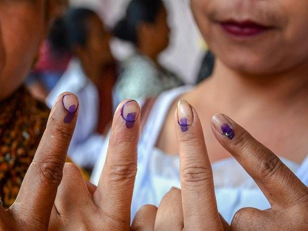 Women voters show their fingers marked with indelible ink after casting vote during the first phase of the general elections, at Umpher in Ri-Bhoi district