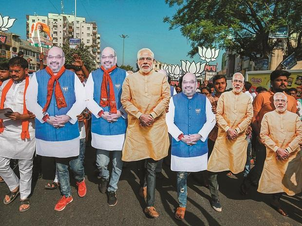 BJP supporters hold cut-outs of Prime Minister Narendra Modi and party president Amit Shah during an election rally in Ahmedabad on Thursday | Photo: PTI