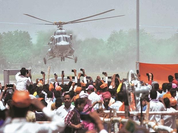 BJP supporters wave towards the helicopter of Prime Minister Narendra Modi as he leaves after an election campaign rally, in Muzaffarpur : Photo: PTI