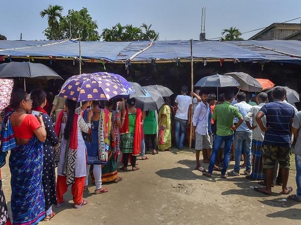 Voters holding umbrella,s to shield themselves from the sun, wait to cast votes at a polling station during the fifth phase of Lok Sabha elections in Barrackpore Monday
